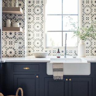 Idee per una grande sala lavanderia tradizionale con lavello stile country, ante con riquadro incassato, ante blu, top in quarzite, pareti bianche, pavimento con piastrelle in ceramica, lavatrice e asciugatrice affiancate e pavimento bianco