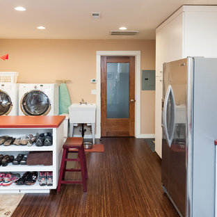 Idéer för mellanstora eklektiska parallella grovkök, med en allbänk, släta luckor, vita skåp, laminatbänkskiva, orange väggar, bambugolv och en tvättmaskin och torktumlare bredvid varandra