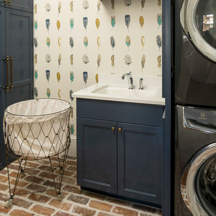 Esempio di una piccola sala lavanderia classica con ante con riquadro incassato, ante blu, top in quarzo composito, pareti multicolore, pavimento in mattoni, lavatrice e asciugatrice a colonna e lavello sottopiano