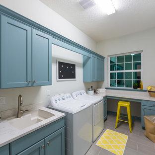 Esempio di una grande sala lavanderia tradizionale con lavello sottopiano, ante in stile shaker, ante blu, lavatrice e asciugatrice affiancate, top in quarzo composito, pareti grigie, pavimento con piastrelle in ceramica e top bianco