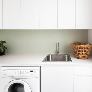 This is an example of a contemporary single-wall dedicated laundry room in Melbourne with a drop-in sink, flat-panel cabinets, white cabinets, white walls, a side-by-side washer and dryer and white benchtop.