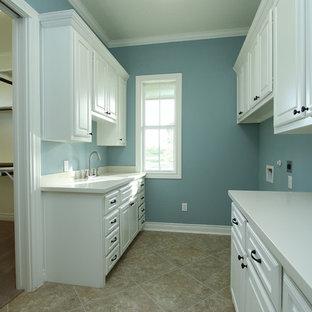 Foto di una lavanderia multiuso stile americano con ante con bugna sagomata, ante bianche, top in superficie solida, pareti blu, pavimento in gres porcellanato, lavatrice e asciugatrice affiancate e lavello sottopiano