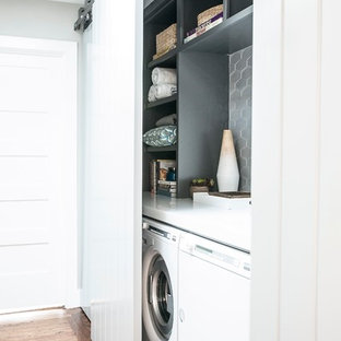 Inspiration for a small contemporary single-wall medium tone wood floor laundry closet remodel in San Francisco with open cabinets, gray cabinets, solid surface countertops, gray walls and a side-by-side washer/dryer