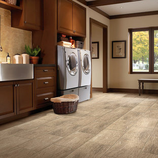 Dedicated laundry room - large contemporary single-wall porcelain tile and brown floor dedicated laundry room idea in Boise with a farmhouse sink, raised-panel cabinets, brown cabinets, beige walls and a side-by-side washer/dryer