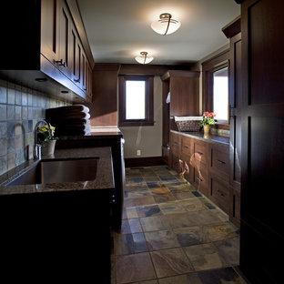 Immagine di una sala lavanderia american style di medie dimensioni con lavello sottopiano, ante in stile shaker, ante in legno scuro, pareti beige e lavatrice e asciugatrice affiancate