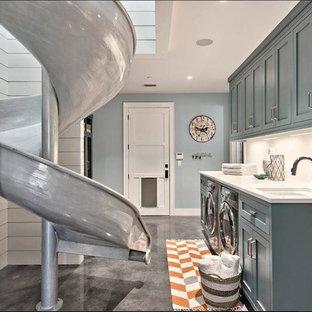 Foto på en funkis tvättstuga, med luckor med infälld panel, turkosa skåp, betonggolv, en tvättmaskin och torktumlare bredvid varandra och grått golv