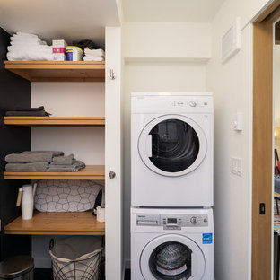 Country l-shaped utility room photo in Portland with an integrated sink, black walls and a stacked washer/dryer