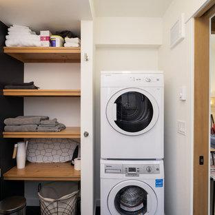 Idée de décoration pour une buanderie champêtre en L multi-usage avec un évier intégré, un mur noir et des machines superposées.