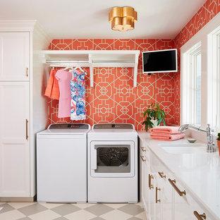 Idées déco pour une buanderie classique dédiée avec un évier encastré, un placard avec porte à panneau encastré, des portes de placard blanches, des machines côte à côte, un sol multicolore, un plan de travail blanc et un mur rouge.