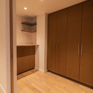 Idéer för funkis tvättstugor, med skåp i ljust trä, träbänkskiva, vita väggar, ljust trägolv, tvättmaskin och torktumlare byggt in i ett skåp och gult golv
