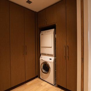 Foto på en funkis tvättstuga, med skåp i ljust trä, träbänkskiva, vita väggar, ljust trägolv, tvättmaskin och torktumlare byggt in i ett skåp och gult golv