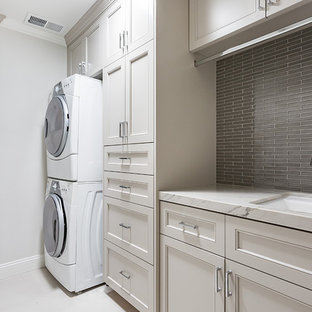 Photo of a transitional single-wall laundry room in San Francisco with an undermount sink, beige cabinets, marble benchtops, grey walls, a stacked washer and dryer, white benchtop and recessed-panel cabinets.