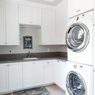 Foto di una grande sala lavanderia country con lavello sottopiano, ante bianche, top in superficie solida, pareti grigie, lavatrice e asciugatrice a colonna, ante in stile shaker e pavimento in compensato