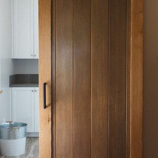 Immagine di una grande sala lavanderia country con lavello sottopiano, ante in stile shaker, ante bianche, top in superficie solida, pareti grigie, pavimento in compensato e lavatrice e asciugatrice a colonna