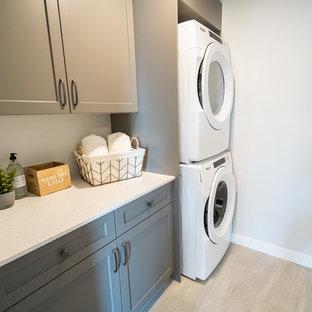 Immagine di una sala lavanderia tradizionale di medie dimensioni con ante in stile shaker, ante grigie, top in quarzo composito, pareti grigie, pavimento in gres porcellanato, lavatrice e asciugatrice a colonna, pavimento beige e top bianco