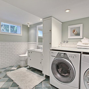 This is an example of a mid-sized l-shaped utility room in Montreal with a drop-in sink, flat-panel cabinets, white cabinets, tile benchtops, terra-cotta floors, a side-by-side washer and dryer and grey walls.