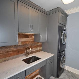Immagine di una sala lavanderia country di medie dimensioni con lavello sottopiano, ante in stile shaker, ante grigie, top in quarzo composito, pareti blu, pavimento in pietra calcarea e lavatrice e asciugatrice a colonna