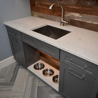 Bild på en mellanstor lantlig tvättstuga enbart för tvätt, med en undermonterad diskho, skåp i shakerstil, grå skåp, bänkskiva i kvarts, blå väggar, kalkstensgolv och en tvättpelare