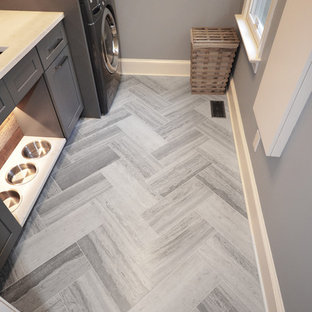 Design ideas for a mid-sized country dedicated laundry room in Charlotte with an undermount sink, shaker cabinets, grey cabinets, quartz benchtops, limestone floors, a stacked washer and dryer and grey walls.