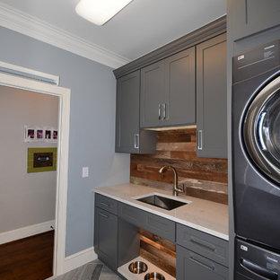 Idéer för mellanstora lantliga tvättstugor enbart för tvätt, med en undermonterad diskho, skåp i shakerstil, grå skåp, bänkskiva i kvarts, blå väggar, kalkstensgolv och en tvättpelare