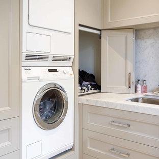 Foto di una grande lavanderia chic con ante in stile shaker, top in marmo e lavatrice e asciugatrice a colonna