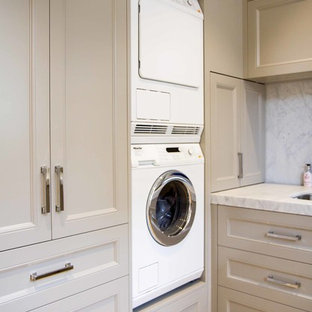 Design ideas for a large classic u-shaped utility room in Melbourne with shaker cabinets, marble worktops and a stacked washer and dryer.