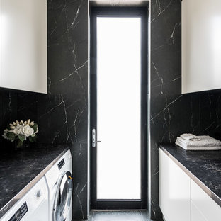 Design ideas for a large contemporary galley separated utility room in Melbourne with a built-in sink, flat-panel cabinets, beige cabinets, engineered stone countertops, black walls, porcelain flooring, a side by side washer and dryer and black floors.