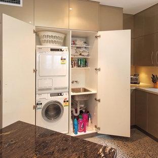 Foto på en liten funkis linjär liten tvättstuga, med en nedsänkt diskho, släta luckor, beige skåp, en tvättpelare och betonggolv