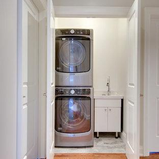 Foto di un piccolo ripostiglio-lavanderia tradizionale con lavello integrato, ante lisce, ante bianche, pareti bianche, pavimento con piastrelle in ceramica e lavatrice e asciugatrice a colonna