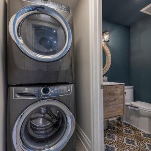 Foto di una piccola lavanderia multiuso minimal con pareti beige, pavimento in gres porcellanato, lavatrice e asciugatrice a colonna e pavimento beige