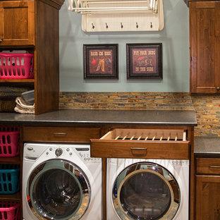 Bild på en mellanstor vintage tvättstuga, med skåp i shakerstil, skåp i mörkt trä, granitbänkskiva, blå väggar, skiffergolv och en tvättmaskin och torktumlare bredvid varandra