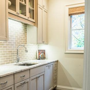 Foto di una lavanderia multiuso stile rurale di medie dimensioni con lavello sottopiano, ante in stile shaker, ante grigie, top in marmo, pareti beige e parquet scuro