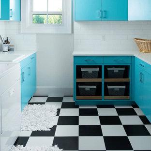 Idéer för en medelhavsstil vita u-formad tvättstuga enbart för tvätt, med en nedsänkt diskho, släta luckor, turkosa skåp, vita väggar, en tvättmaskin och torktumlare bredvid varandra och flerfärgat golv
