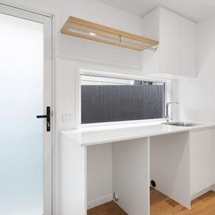 Inspiration för linjära vitt tvättstugor enbart för tvätt, med en nedsänkt diskho, släta luckor, vita skåp, fönster som stänkskydd, en tvättmaskin och torktumlare bredvid varandra och brunt golv