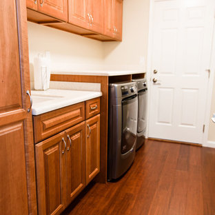 Large traditional single-wall utility room in Seattle with an undermount sink, raised-panel cabinets, medium wood cabinets, solid surface benchtops, beige walls, bamboo floors, a side-by-side washer and dryer and brown floor.