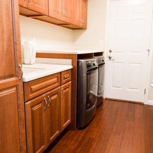 Exempel på ett stort klassiskt linjärt grovkök, med en undermonterad diskho, luckor med upphöjd panel, skåp i mellenmörkt trä, bänkskiva i koppar, beige väggar, bambugolv, en tvättmaskin och torktumlare bredvid varandra och brunt golv