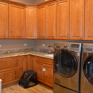 This is an example of a large classic l-shaped utility room in Chicago with a submerged sink, medium wood cabinets, granite worktops, ceramic flooring and a side by side washer and dryer.
