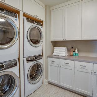 Immagine di una sala lavanderia chic con ante in stile shaker, ante bianche, pareti grigie, lavatrice e asciugatrice a colonna, pavimento beige e top grigio