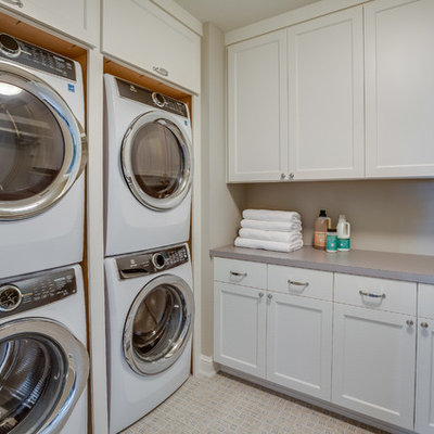Dedicated laundry room - traditional beige floor dedicated laundry room idea in Minneapolis with shaker cabinets, white cabinets, gray walls, a stacked washer/dryer and gray countertops