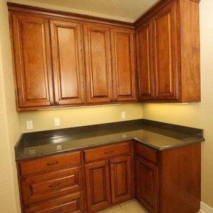 Immagine di una piccola sala lavanderia classica con ante con bugna sagomata, ante in legno scuro, top in granito, pareti beige, pavimento in gres porcellanato, lavatrice e asciugatrice affiancate e pavimento beige