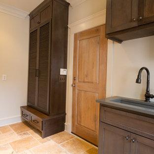 Esempio di una lavanderia tradizionale di medie dimensioni con lavello sottopiano, ante a persiana, ante in legno bruno e pavimento in travertino