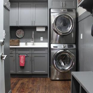 Klassisk inredning av en mellanstor linjär tvättstuga enbart för tvätt, med en nedsänkt diskho, skåp i shakerstil, grå skåp, vita väggar, mörkt trägolv och en tvättpelare