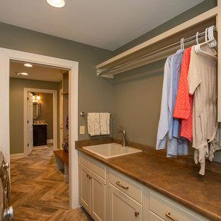 Ispirazione per una sala lavanderia classica di medie dimensioni con lavello da incasso, ante in stile shaker, ante bianche, pareti verdi, lavatrice e asciugatrice affiancate e pavimento marrone