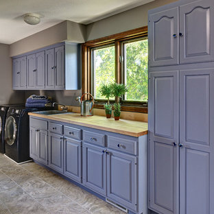 Mid-sized elegant single-wall ceramic tile dedicated laundry room photo in Minneapolis with a drop-in sink, raised-panel cabinets, blue cabinets, wood countertops, gray walls and a side-by-side washer/dryer