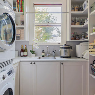 Inspiration for a mid-sized transitional u-shaped utility room in Sydney with shaker cabinets, white cabinets, quartz benchtops, grey splashback, ceramic splashback, white benchtop, a drop-in sink and a stacked washer and dryer.