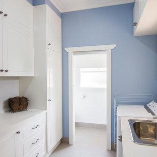 Klassisk inredning av en mellanstor parallell tvättstuga enbart för tvätt och med garderob, med en enkel diskho, skåp i shakerstil, vita skåp, granitbänkskiva, blå väggar, travertin golv och beiget golv