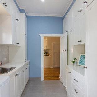 На фото: отдельные, параллельные прачечные среднего размера в стиле современная классика с одинарной раковиной, фасадами в стиле шейкер, белыми фасадами, гранитной столешницей, синими стенами, полом из травертина и бежевым полом