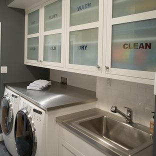 Exemple d'une buanderie chic avec un évier posé, un placard à porte vitrée et des machines côte à côte.