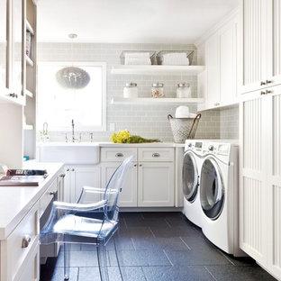 Idee per una lavanderia multiuso tradizionale di medie dimensioni con top in quarzo composito, lavello stile country, ante in stile shaker, ante bianche, lavatrice e asciugatrice affiancate, pavimento nero e top bianco