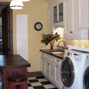Design ideas for a classic utility room in San Diego with composite countertops, white cabinets, multi-coloured floors and black worktops.